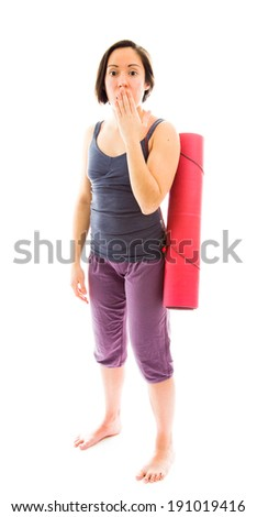 Young woman carrying exercise mat with hand over her mouth and shock - stock photo