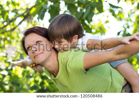 Young woman carrying her daughter - stock photo