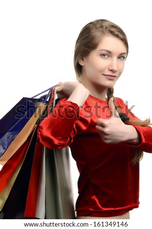 Young woman carrying many shopping bags, thumbs up. Girl shopping isolated on white. - stock photo