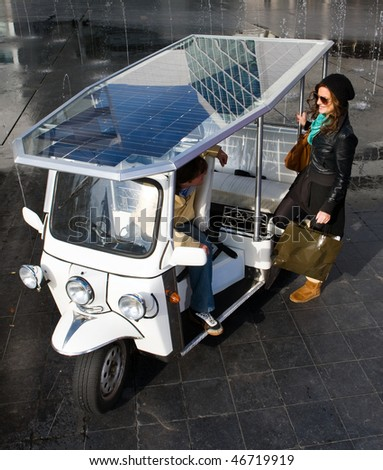 Young woman catching a ride in a solar powered tuc tuc - stock photo