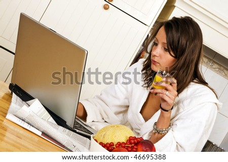 Young woman, catching up with the day's events on her laptop whilst drinking a glass of orange jus, wearing a bathrobe - stock photo