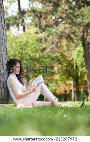 Young woman caucasian asian leaning against a tree and sitting in the grass reading a book in the park - stock photo
