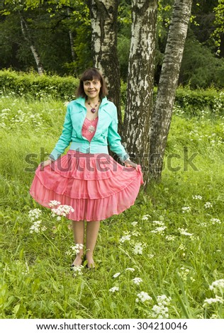 Young woman (Caucasian, brunette) standing near birch trees in park. - stock photo