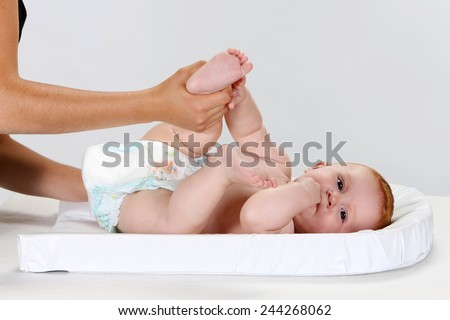 Young woman changing a baby's diaper - stock photo