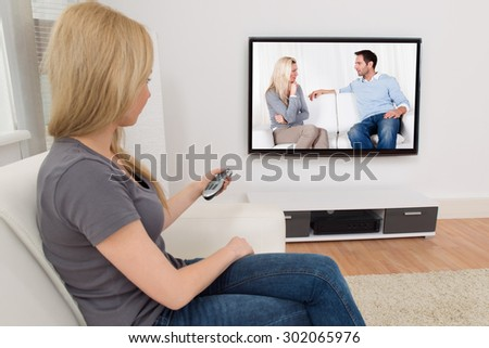 Young Woman Changing Channel With Remote Control In Front Of Television