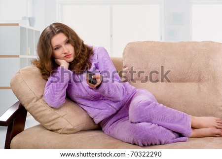 Young woman changing TV channels with remote control sitting on sofa at home - stock photo