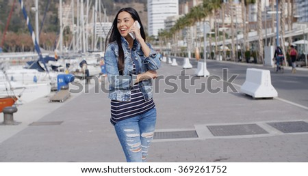 Young woman chatting on her phone in the street - stock photo