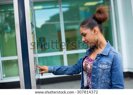 young woman checking a map in the street - stock photo