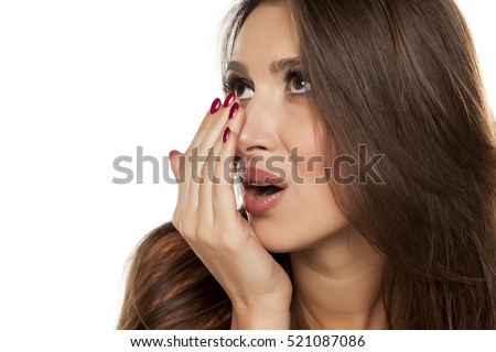 young woman checking her breath with a hand
