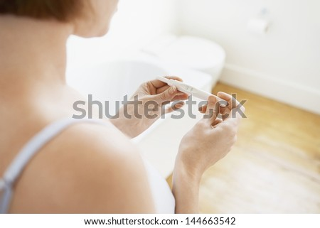 Young woman checking pregnancy test kit in bathroom - stock photo