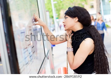 young woman checking the timetable at the bus stop