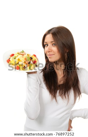 Young woman chef holding the plate with italian lemon pappardelle, tagliatelle, macaroni, spaghetti pasta with tomato, shrimps and olives on it in hand on a white background. Healthy food concept