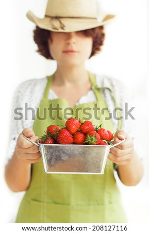 Young woman chef holds metal box with strawberry