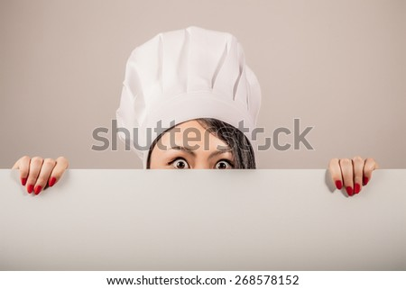 Young woman chef wearing a white toque holding a blank white sign in her hands and peeking over the top with just her eyes showing and a surprised shocked expression - stock photo