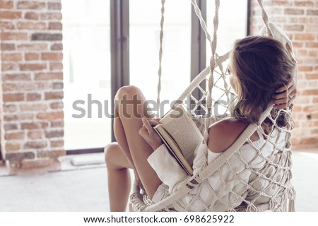 Young woman chilling at home in comfortable hanging chair. Girl relaxing and reading book in swing in loft living room with brick walls.