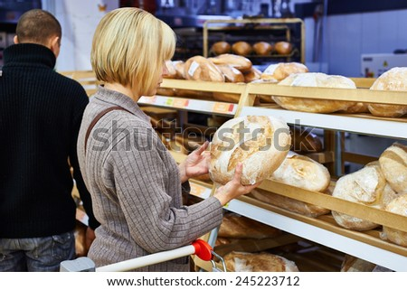 Young woman chooses bread in the store - stock photo