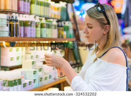Young woman choosing cosmetic cream in beauty shop. - stock photo
