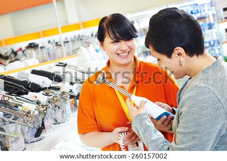 Young woman choosing electric blender in home appliance shopping mall supermarket - stock photo
