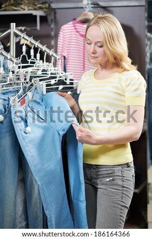 Young woman choosing jeans during clothing shopping at store - stock photo