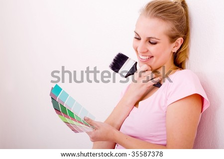 young woman choosing paint color for the new home - stock photo