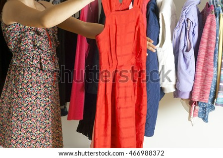 Young woman choosing red dress on a rack in a showroom. Shopping concept
