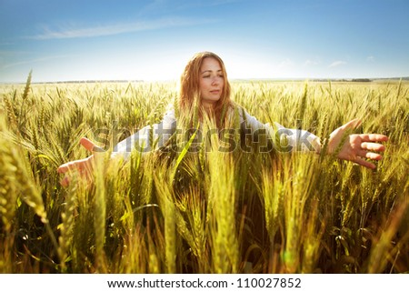 Young woman clasped her hands and ears of wheat