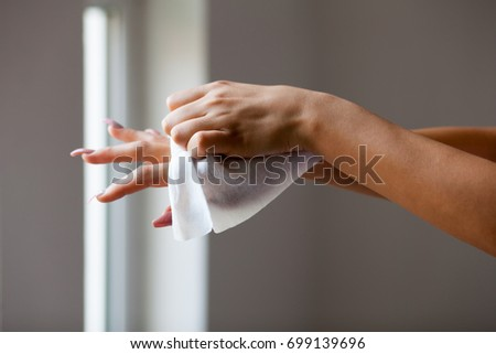 Young woman clean hands with wet wipes