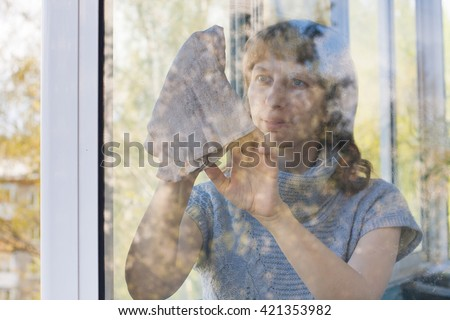 young woman cleaning a window