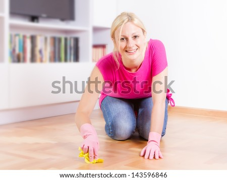 Young woman cleaning and mopping floor at home.