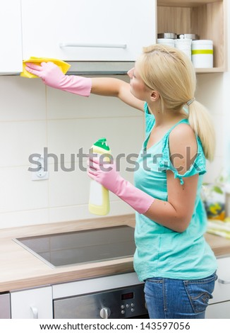 Young woman cleaning furniture in the kitchen. - stock photo