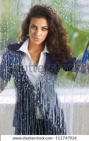 Young woman cleaning her windows with squeegee cleaning - stock photo