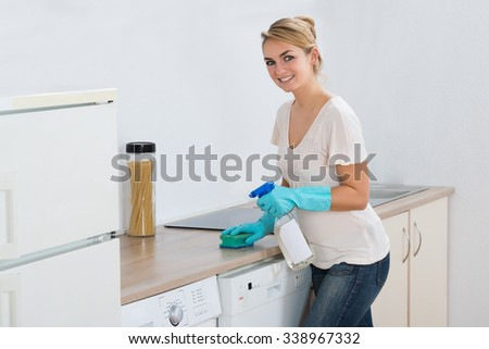 Young woman cleaning kitchen counter with sponge at home - stock photo