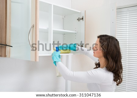 Young Woman Cleaning Shelf With Rag And Detergent Spray Bottle - stock photo
