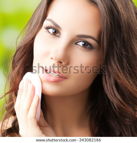 young woman cleaning skin by cotton pad