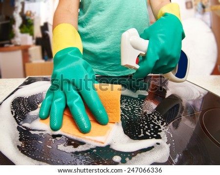 Young woman cleaning stove in her kitchen - stock photo