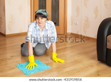 young woman cleaning the floor with a rag