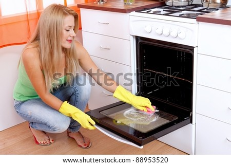 Young woman cleaning the oven with a sponge in the kitchen - stock photo