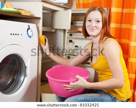 Young woman  cleaning the refrigerator at her kitchen - stock photo