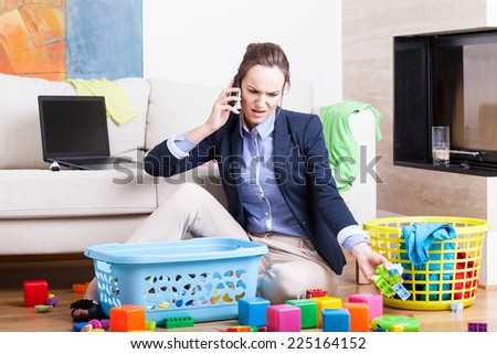 Young woman cleaning up toys and working from home - stock photo