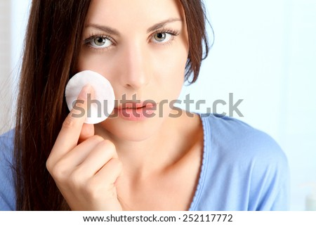 young woman cleanses her face - stock photo