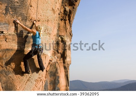 Young woman climbing a rock of sandstone - stock photo