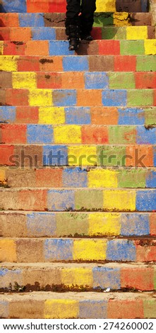 Young woman climbing colorful stairs - stock photo