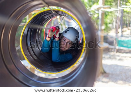 young woman climbing in a barrel with a rope, in an adventure park - stock photo