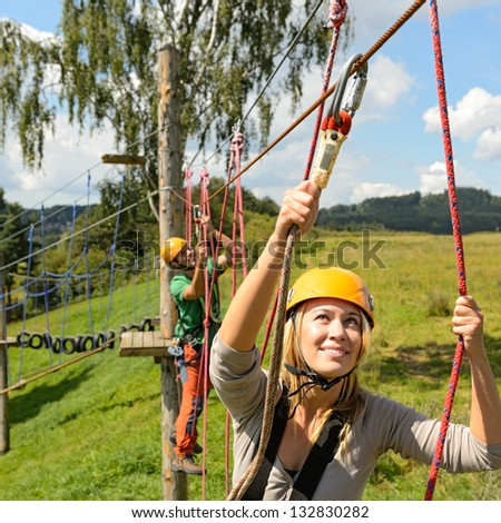 Young woman climbing in adventure park with friend summer free time - stock photo