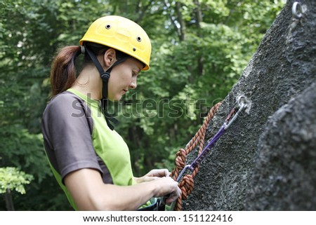Young woman climbing on a limestone wall, rock climbing in mountains with natural background. - stock photo