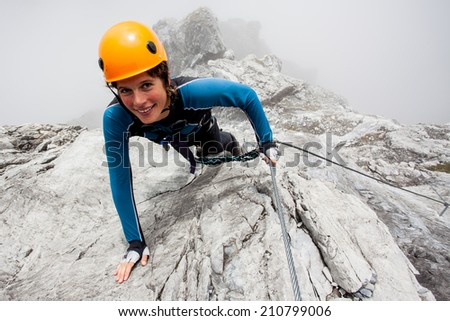 Young woman climbing steep rock wall - stock photo