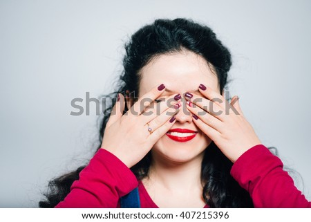 Young woman closes eyes with her hands, wearing a overalls, close-up isolated on a gray background - stock photo