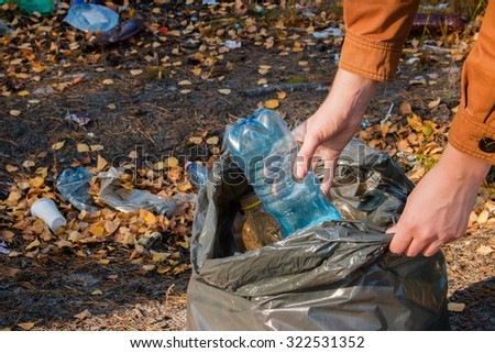young woman collects garbage in the woods - stock photo