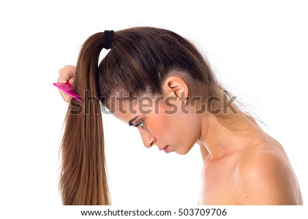 Young woman combing her long ponytail
