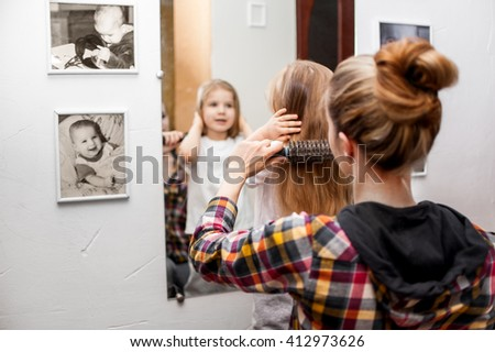 Young woman combing white child five years old near the mirror - stock photo